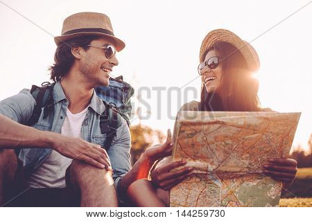 Finding their own way. Low angle view of beautiful young couple with backpacks examining map together and smiling while sitting on green grass outdoors