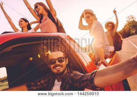 Capturing bright moments. Group of young cheerful people having fun in pick-up truck while driver making selfie