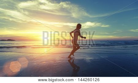 Running silhouette of young girl on the sea beach during an amazing sunset. Healthy way of life.