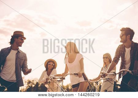 Carefree talk with friends. Low angle view of cheerful young people talking while standing near their bicycles on the road