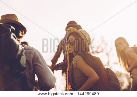 Travelling with friends. Group of young people with backpacks walking together and looking happy