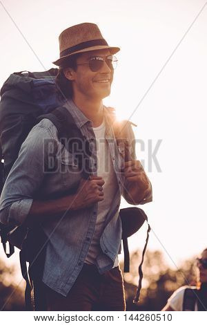 Enjoying early morning hike. Handsome young man in fedora carrying backpack and smiling while walking outdoors