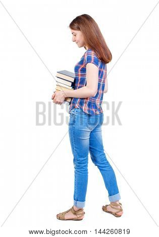 Girl carries a heavy pile of books. back view. Girl in plaid shirt standing sideways and holding a stack of books.
