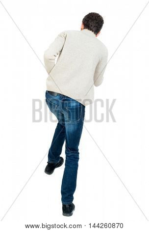 back view of guy funny fights waving his arms and legs. Rear view people collection. backside view of person. Curly short-haired man in a woolen white jacket jumping on one leg.