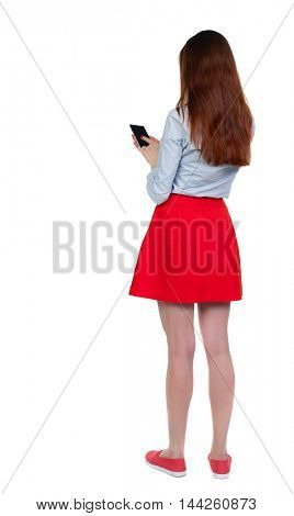 back view of standing young beautiful woman using a mobile phone or tablet computer. girl watching. Long-haired brunette in red skirt presses a finger on a smartphone.