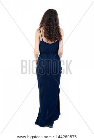 back view of standing young beautiful woman. dark curly girl in a blue evening dress is holding the dress.