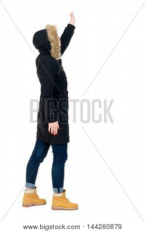 Back view of beautiful woman welcomes. Girl in warm winter black jacket stands sideways and waving.