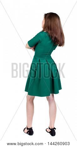 back view of standing young beautiful woman. girl watching. slender brunette in a green short dress stands with his arms crossed.