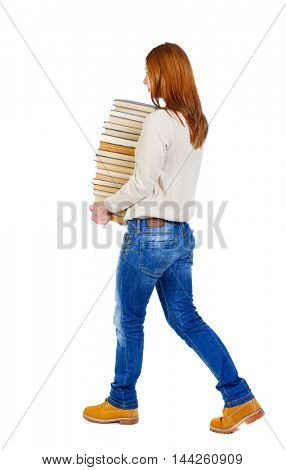 Girl comes with stack of books. side view. girl in a white warm jacket bears a huge stack of books