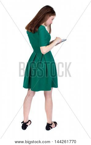 back view of standing young beautiful woman using a mobile phone or tablet computer. girl watching. slender brunette in a green short dress dials number on phone.