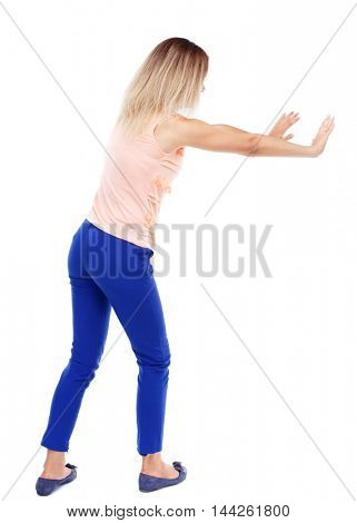 back view of woman pushes wall. Isolated over white background. Blonde in blue pants shoves something with his hands.