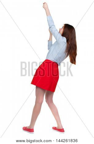 back view of standing girl pulling a rope from the top or cling to something. Long-haired brunette in red skirt hung on a rope.