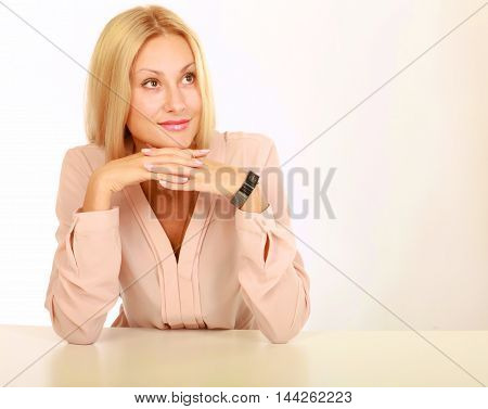 Young natural woman with clean face sitting at white table leaning on her elbows, over white background.