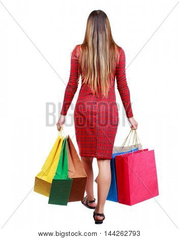 back view of going woman with shopping bags . girl in red plaid dress goes away with paper bags.