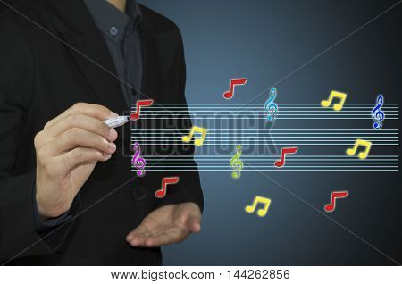 businessman hand holding pen writing music notes