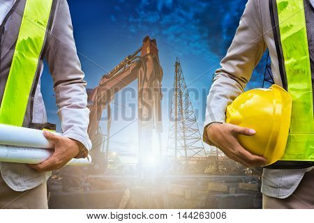 Engineer holding construction drawing and Safety officer holding hard hat with construction machine at night in the background