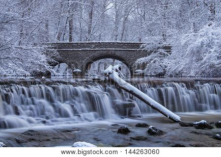 Snow Covered Trees Framing A Stone Bridge And Waterfall During Winter In The Park Sharon Woods Southwestern Ohio USA