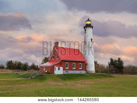 A very cute Lighthouse The Tawas Point Lighthouse on a stormy autumn evening in the Tawas Point State Park with Lake Huron to one side and Tawas Bay on the other Lower Peninsula Michigan; USA