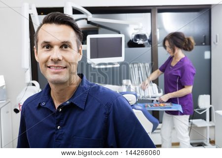 Dentist Smiling While Assistant Working At Clinic