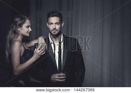 Rich macho young man drink whiskey with blonde lover at night james bond