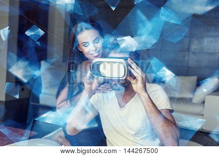 Casual caucasian man with VR headset and woman indoors blue glowing polygons