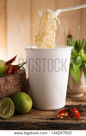 Cup noodle Cooked instant cup noodle with ingredient on wood background