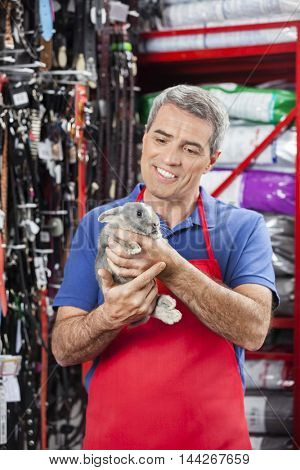 Happy Salesman Looking At Rabbit In Pet Store