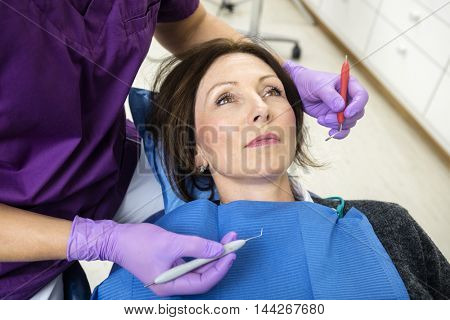 Female Dentist Examining Patient With Tools In Clinic