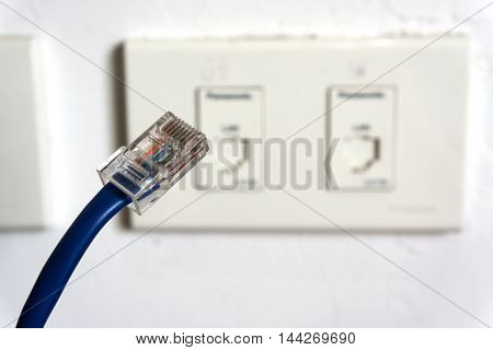 LAN Cable plug to wall outlet for computer network.