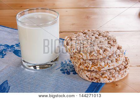 Milk In Glass Mug With Crispbread On Wooden Table.