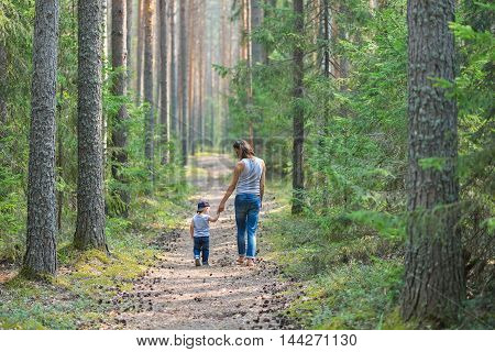 Mother and baby walk on country rural road in pine forest.