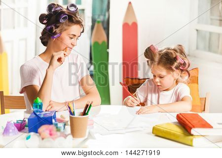 The young mother and her daughter drawing with pencils at home