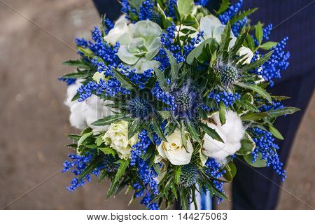 Beautiful wedding bouquet of flowers in hands of the bride wedding bouquet and rings
