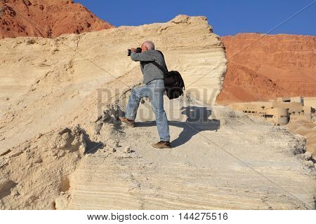 Yellow clay canyon in Dead Sea. An elderly white-haired man with a passion photographs.