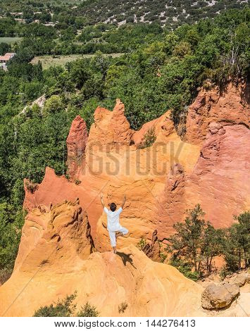 Orange and red picturesque hills in Roussillon. The elderly woman in special form of yoga  performs asana Tree