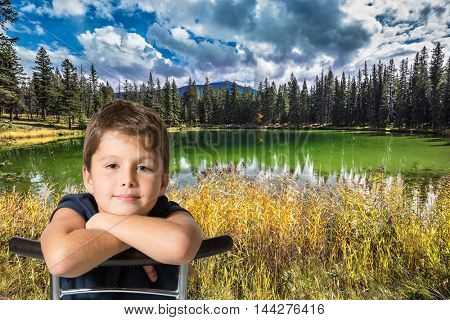 Handsome boy sitting on the shore of small lake. The yellow and orange autumn grass and trees. Rocky Mountains of Canada