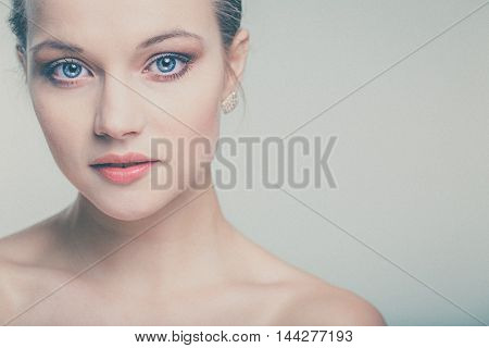 Beautiful young woman with perfect skin and face (color toned image with added grain)