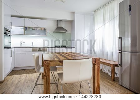 Modern Kitchen Interior Design Architecture Stock Image, Photo of a modern white kitchen with a dark wood table, hi-end appliances and plenty of daylight