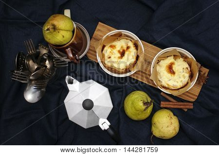 Still life with cottage cheese casserole with pears on wooden desk against deep blue table cloth. Low key.