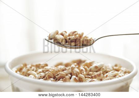 Spoon serving some cereals from a bowl at breakfast. Empty copy space for Editor's text.