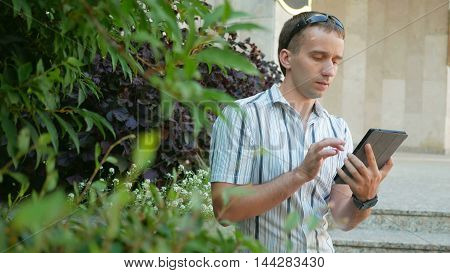 Outdoor portrait of modern young man with digital tablet. Man in sunglasses and jacket. Around a lot of green plants.