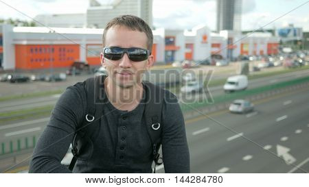 Young handsome man in a nice fitting clothes removes and wears sunglasses. urban landscape.