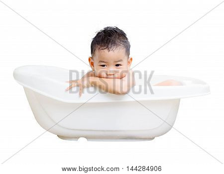 happy baby boy is bathed in white bath