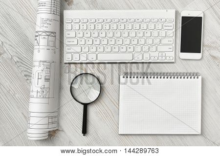 Office workspace with architectural drawing, keyboard, smarthphone, clean book and magnifier on wooden surface in top view. Workplace with modern technology. Engineering work. Construction and architecture.