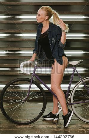 girl in jeans jacket holding the tail of the hair and is sitting on a bicycle in the studio