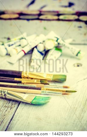 Artist paint brushes and oil paint tubes on white wooden background.