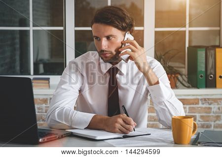 Handsome Young Businessman Sitting At His Workplace Writing A Note And Talking On The Smartphone. Business Theme