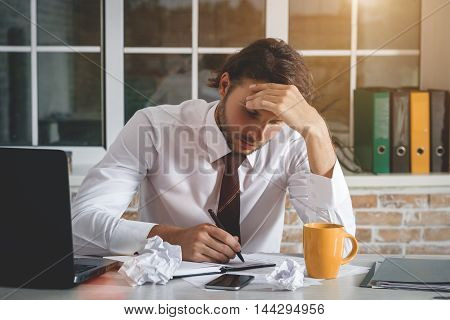 Sad Young Businessman Sitting At His Workplace And Write A Note. Business Theme