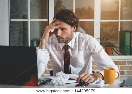 Sad Young Businessman Sitting At His Workplace Looking At His Laptop And Write A Note. Business Theme