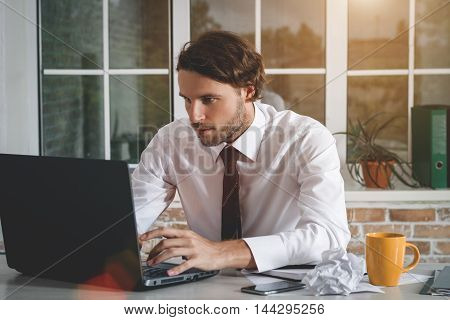 Handsome Young Businessman Sitting At His Workplace Looking At His Laptop. Business Theme